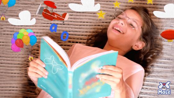 Niña leyendo un libro y sonriendo